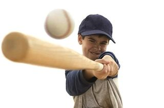 Boy_swinging_baseball_bat_at_ball_bld005810
